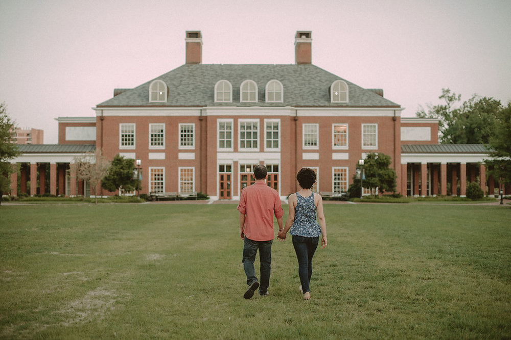 Couple walking away from camera on lawn