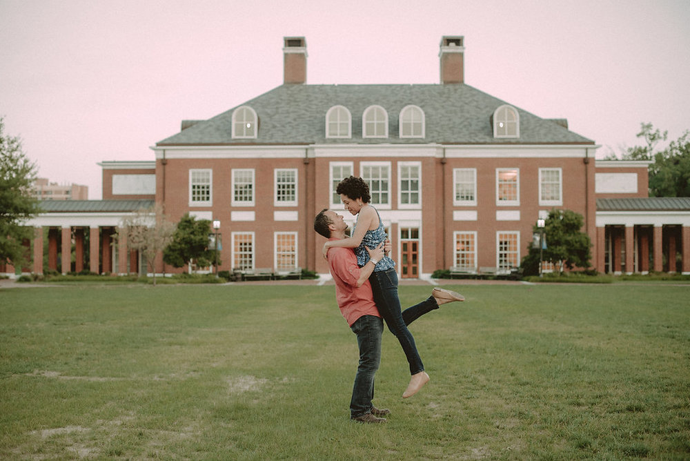 Man lifting woman on lawn