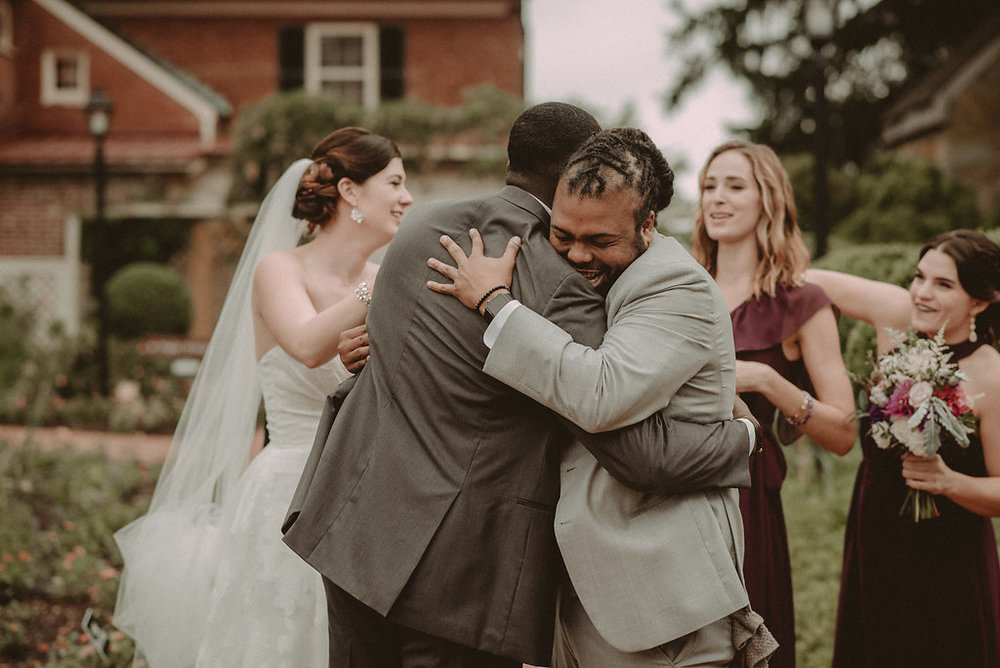 Brie and groom hugging wedding party