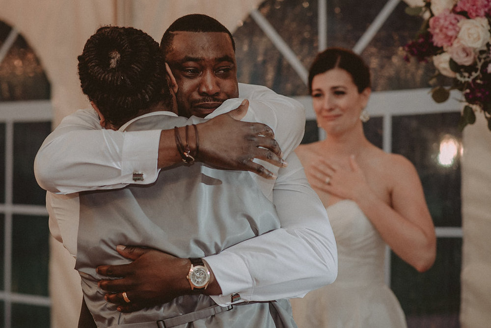 Groom and groomsmen hugging at reception