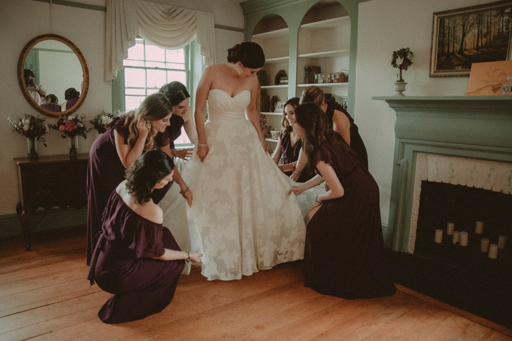 Bridesmaids help bride get dressed