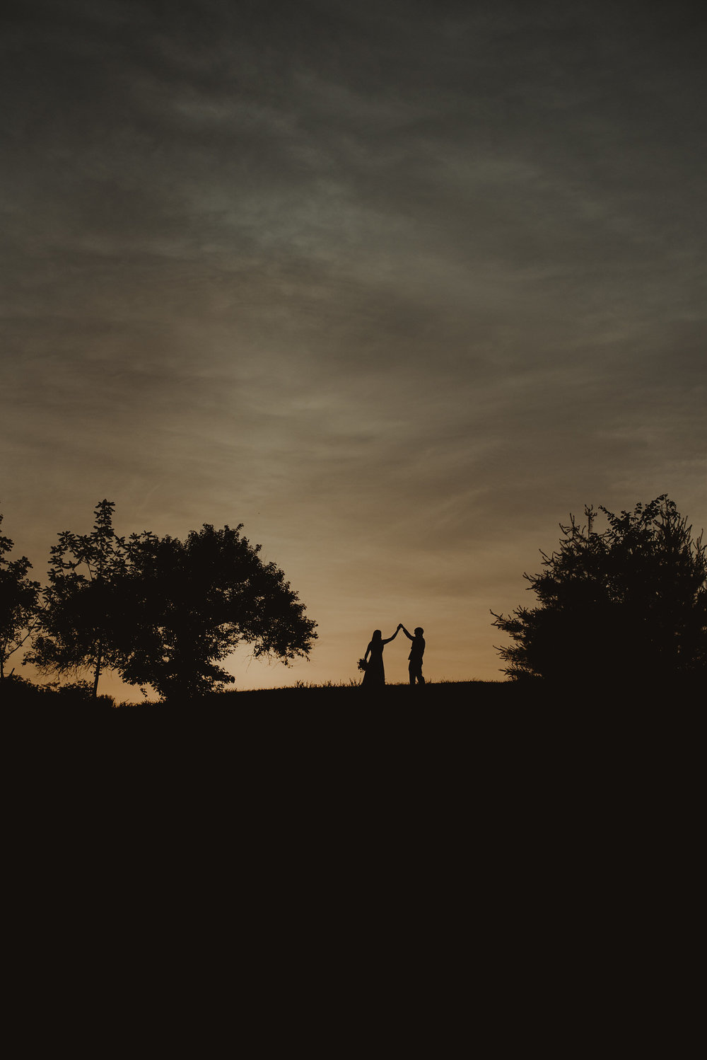 Bride and groom on a hill at night