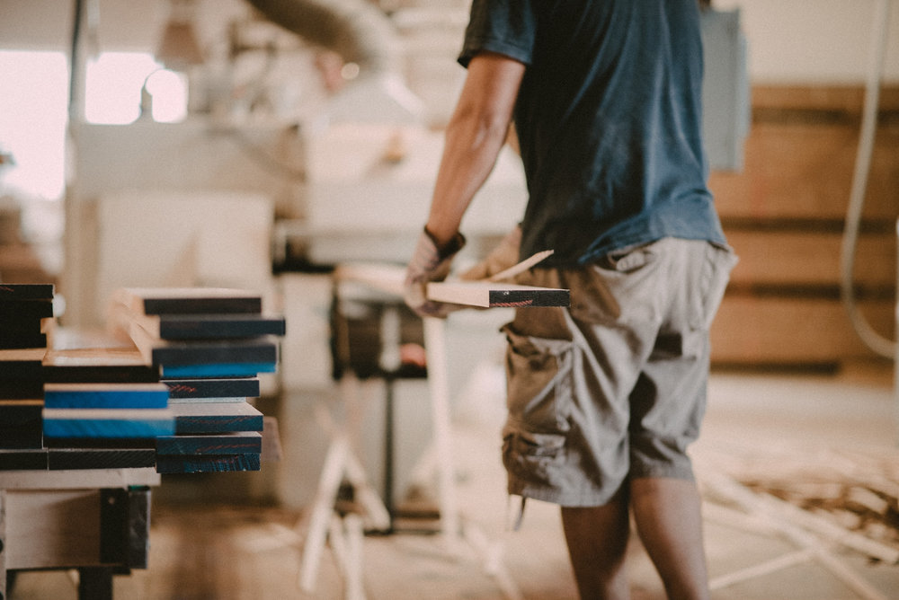 Man lifting wood in workshop