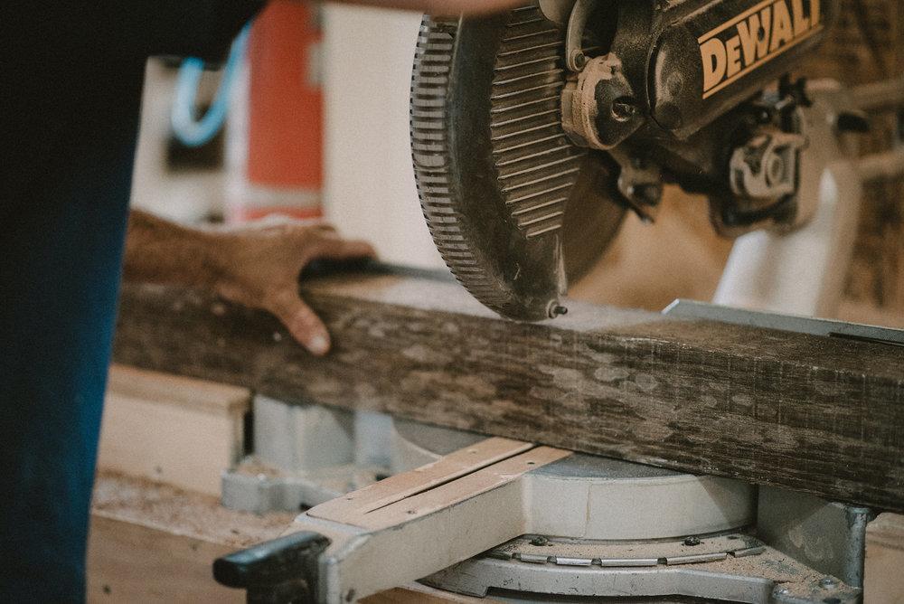 Man sawing raw lumber