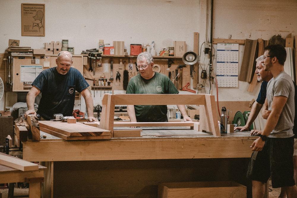 Men gathered around table in workshop