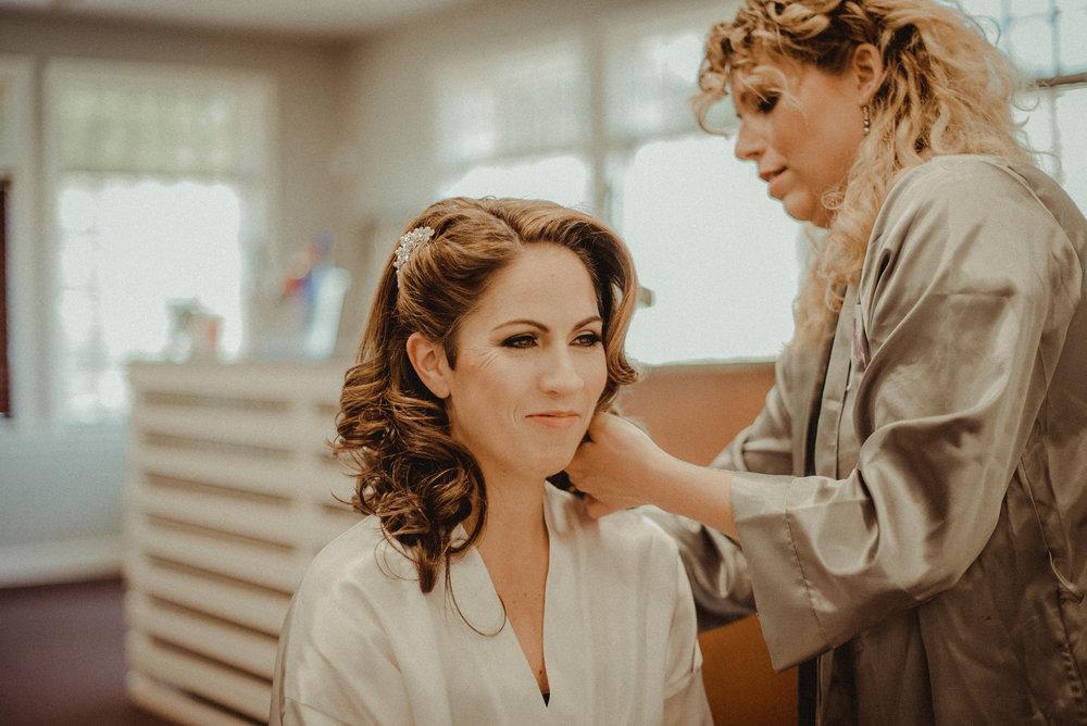 Bridesmaid helping bride fix hair