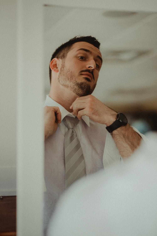 Groom fixing tie in mirror