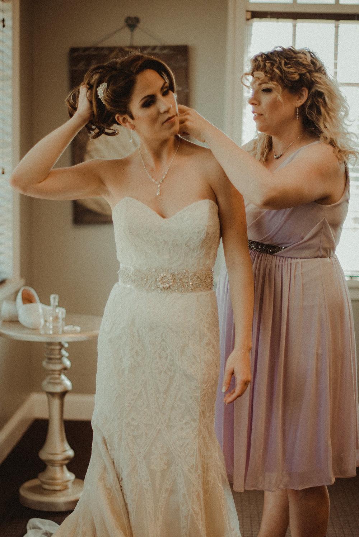 Bridesmaid helping bride get ready