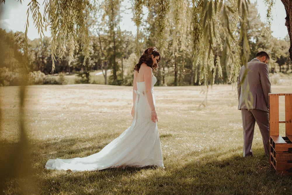 Bride walking toward groom under tree