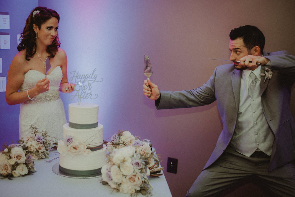 Bride and groom posing before cutting cake