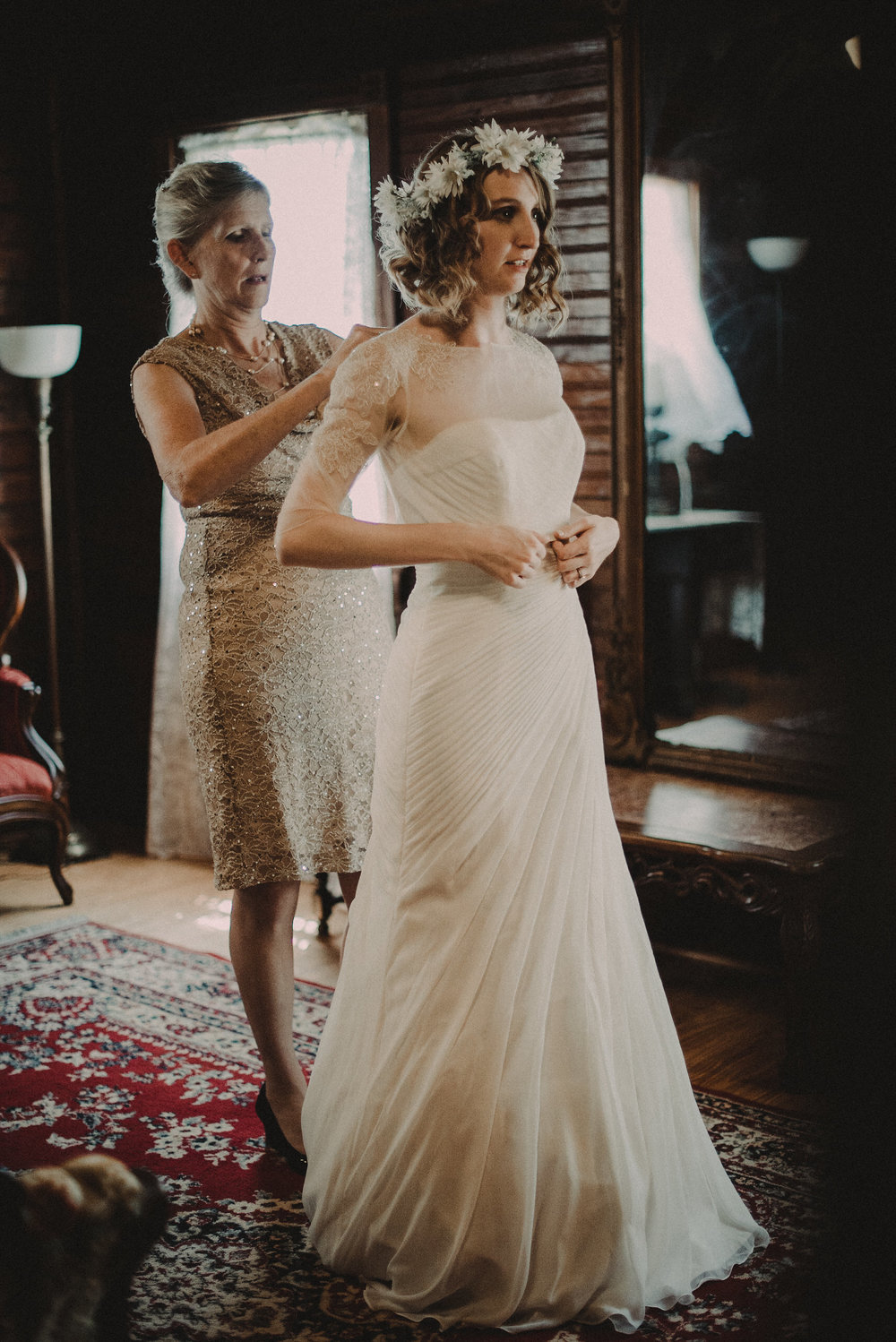 Mother helping bride get dressed