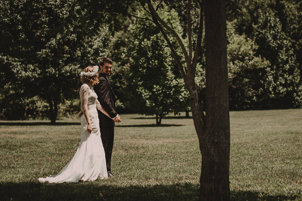 Bride and groom holding hands under tree