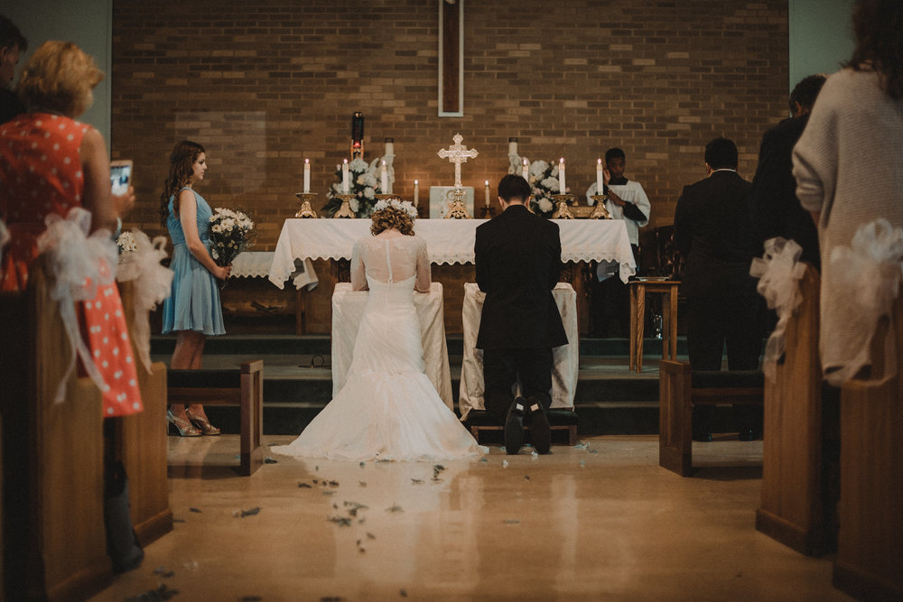 Bride and groom kneeling at altar