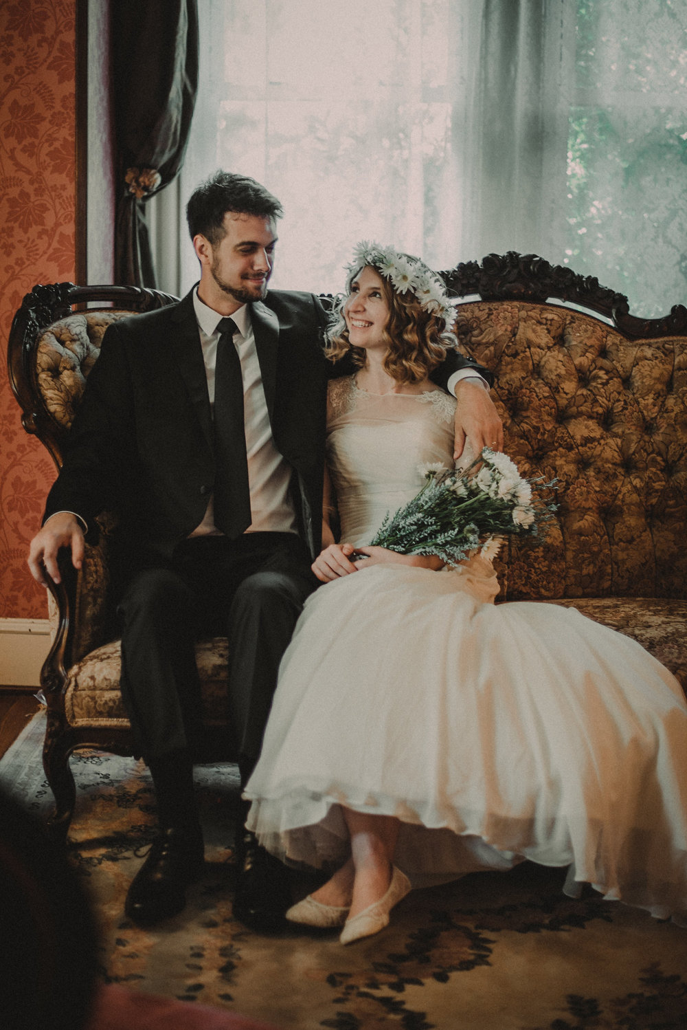 Bride and groom sitting on couch together