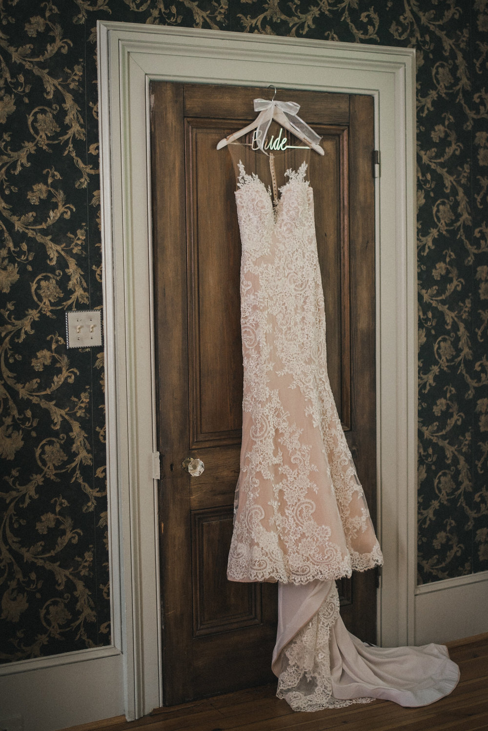Wedding dress hanging on the back of a door