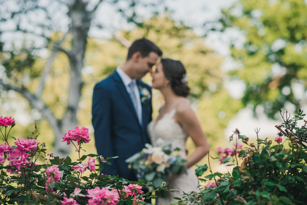 Bride and groom behind flowers