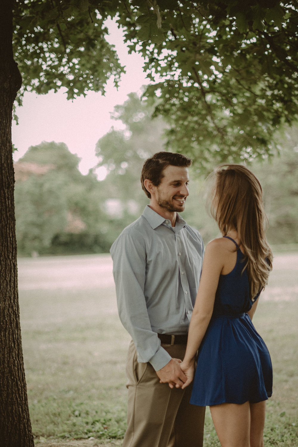 Couple holding hands under tree