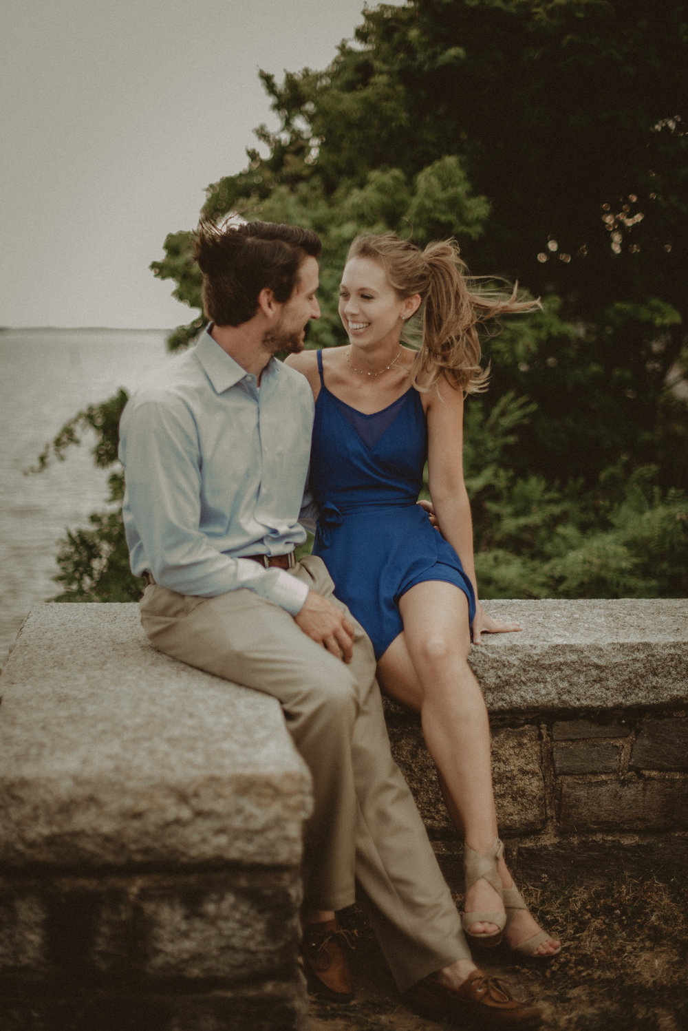 Couple sitting on stone wall in wind