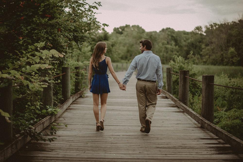 Couple walking away on wooden bridge