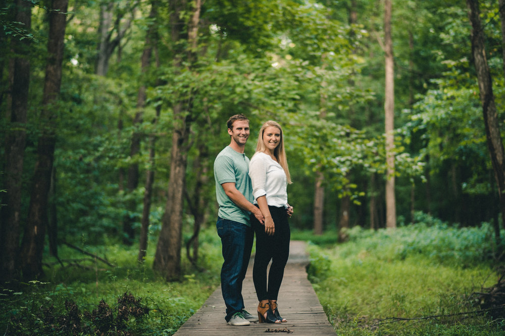 Man and woman standing on trail in forest
