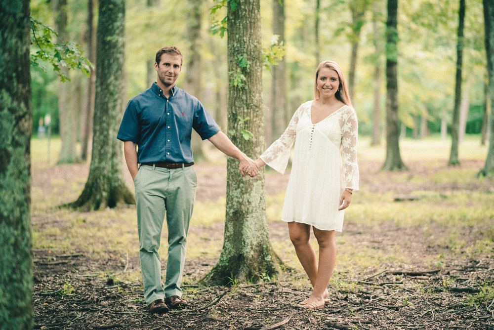 Couple holding hands by tree