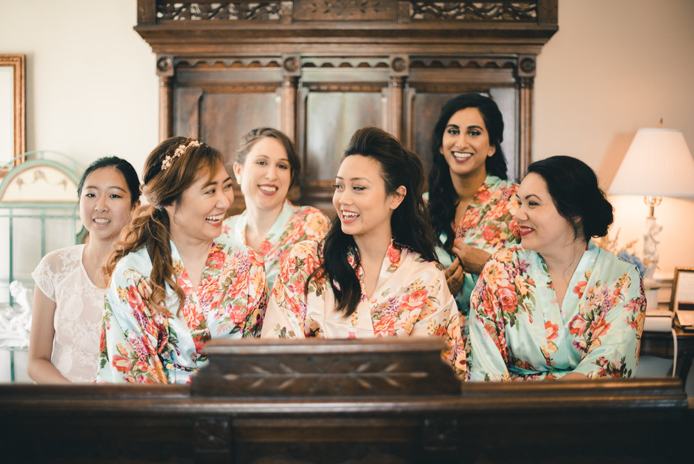 Bride and bridesmaids in robes on bed