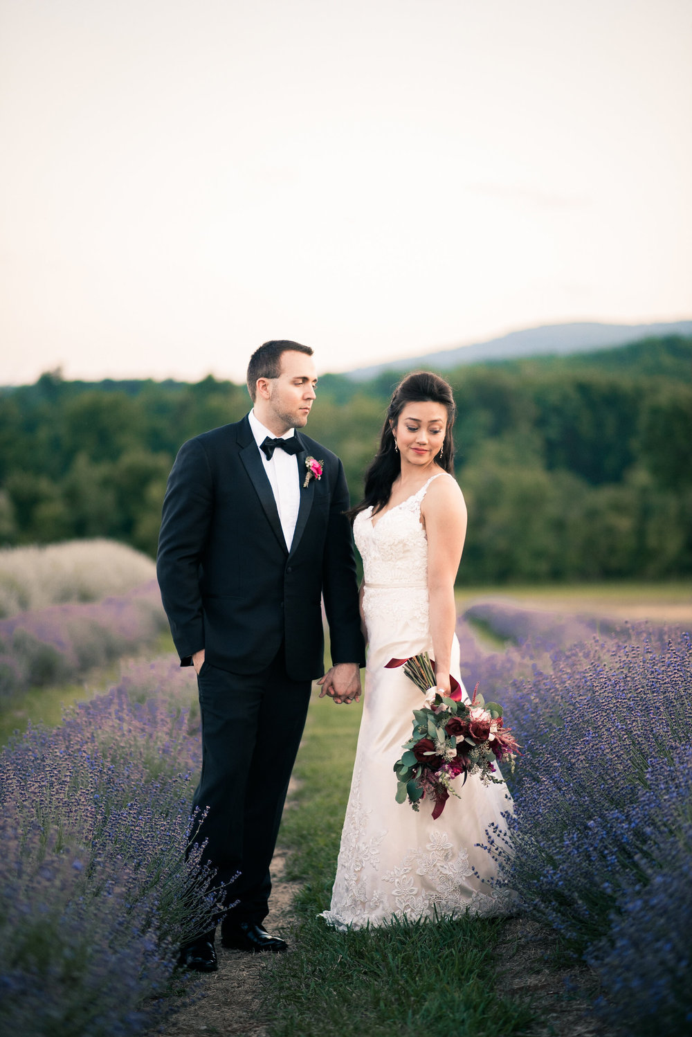 Groom looking at bride in lavender field