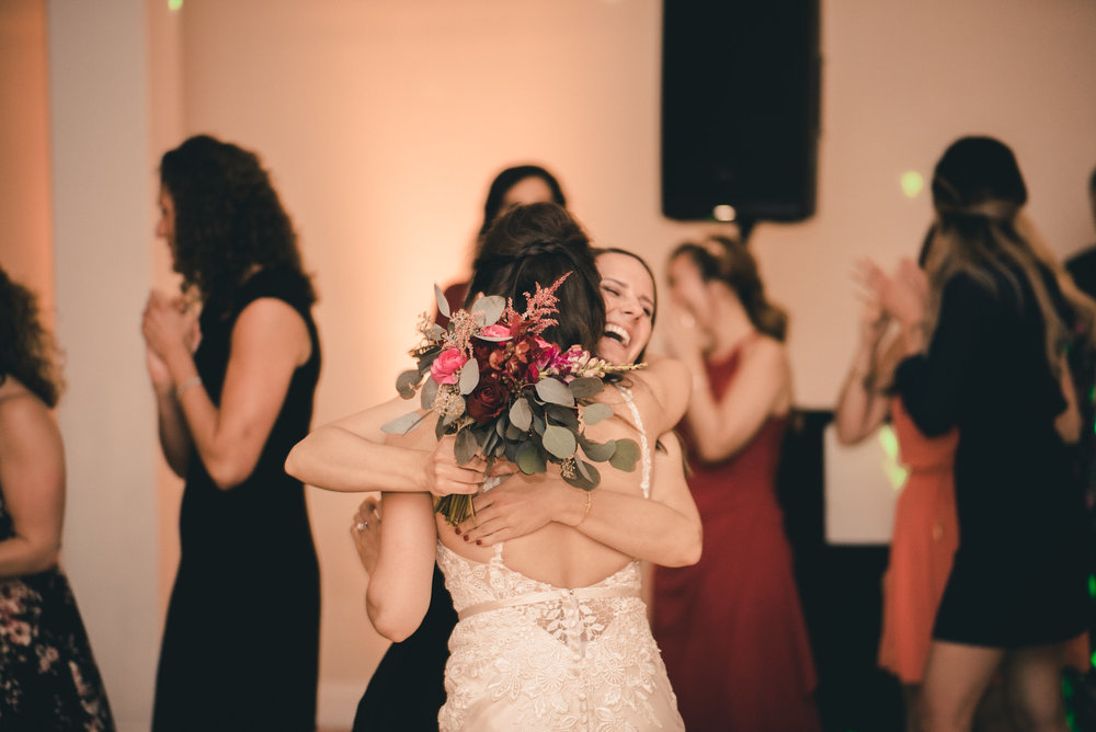 Bride hugging bouquet catcher