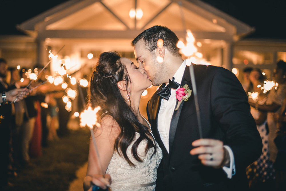 Bride and groom kissing and holding sparklers