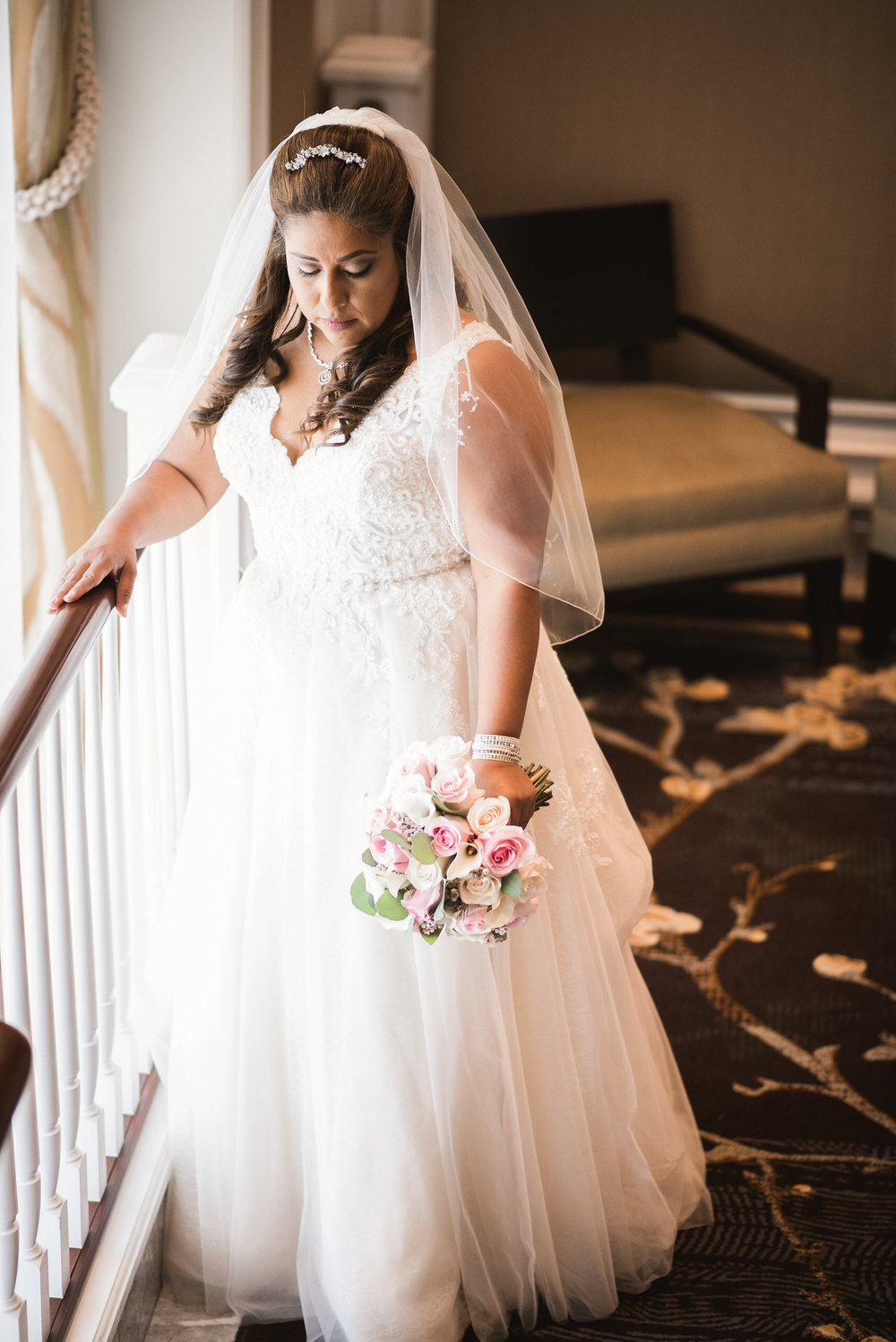 Bride standing by railing with bouquet