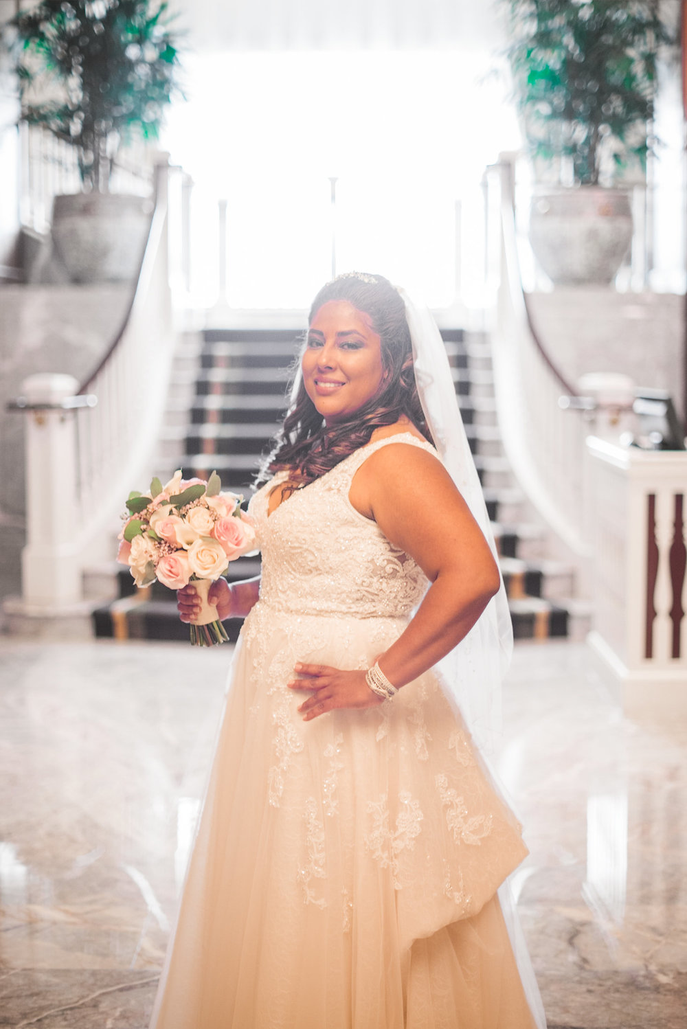 Bride standing in front of stairs in sun