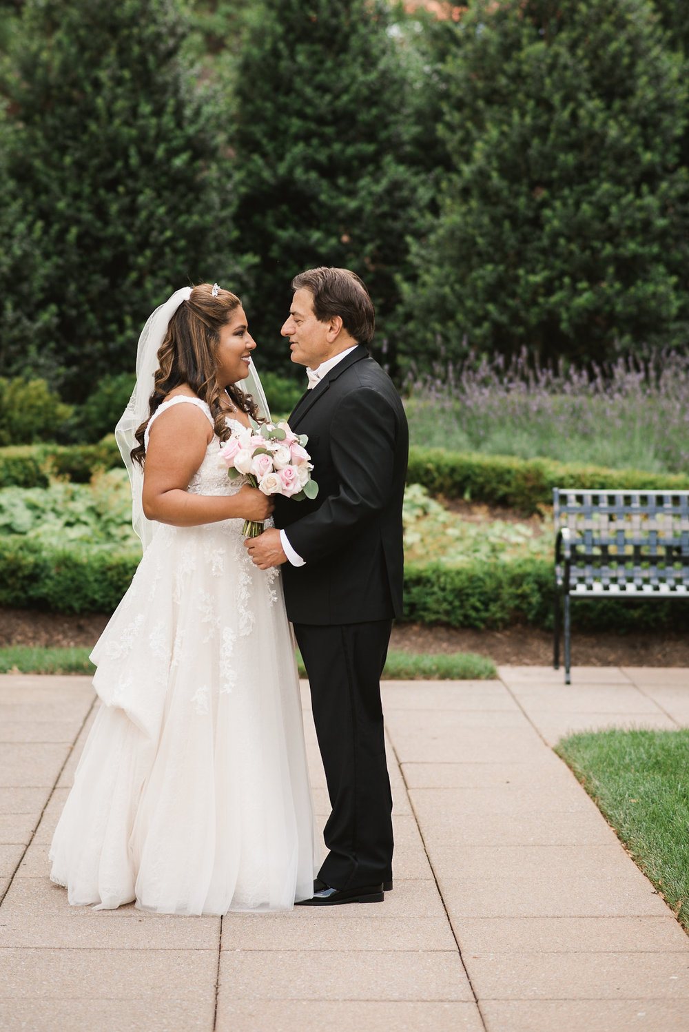 Bride and groom facing one another in courtyard