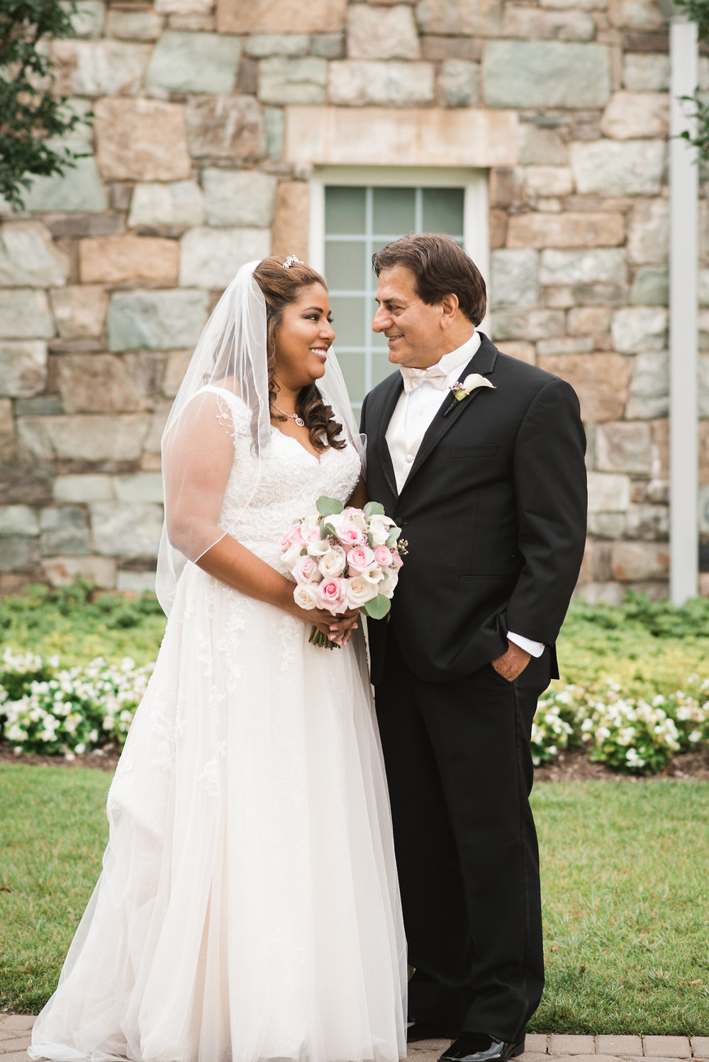 Bride and groom in front of stone building