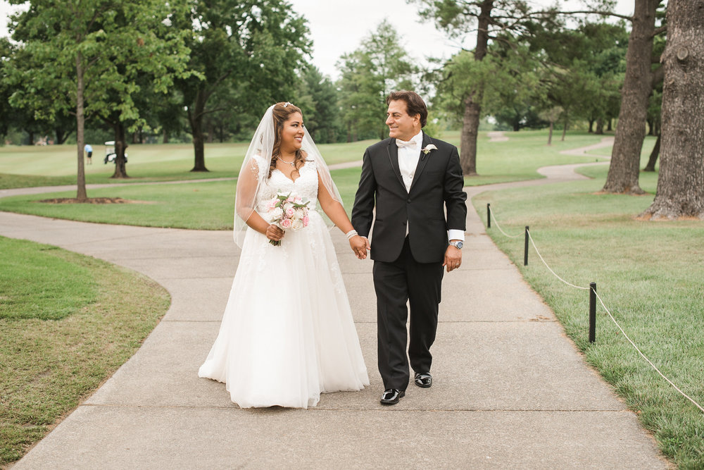 Bride and groom walking down sidewalk