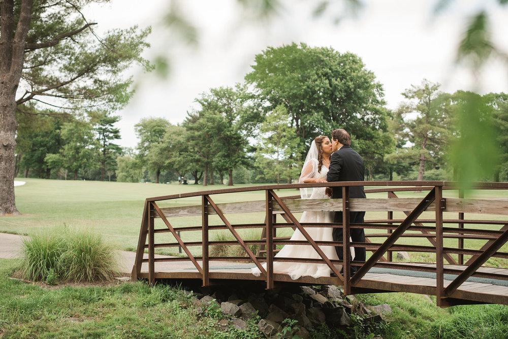 Bride and groom standing on bridge
