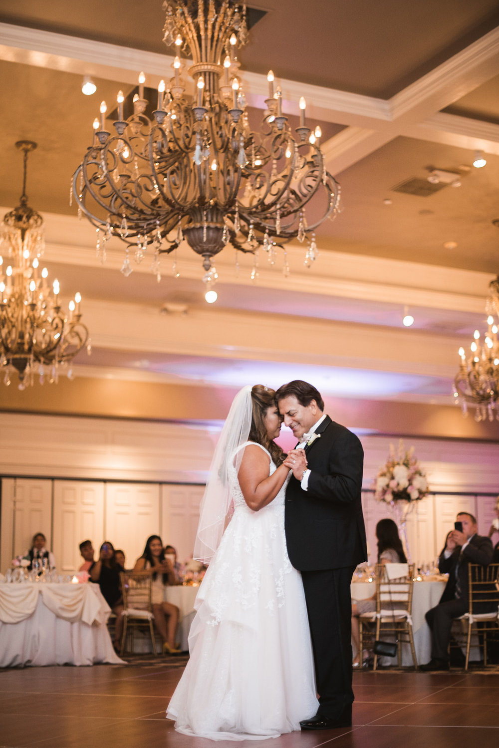 Bride and groom dancing under chandelier