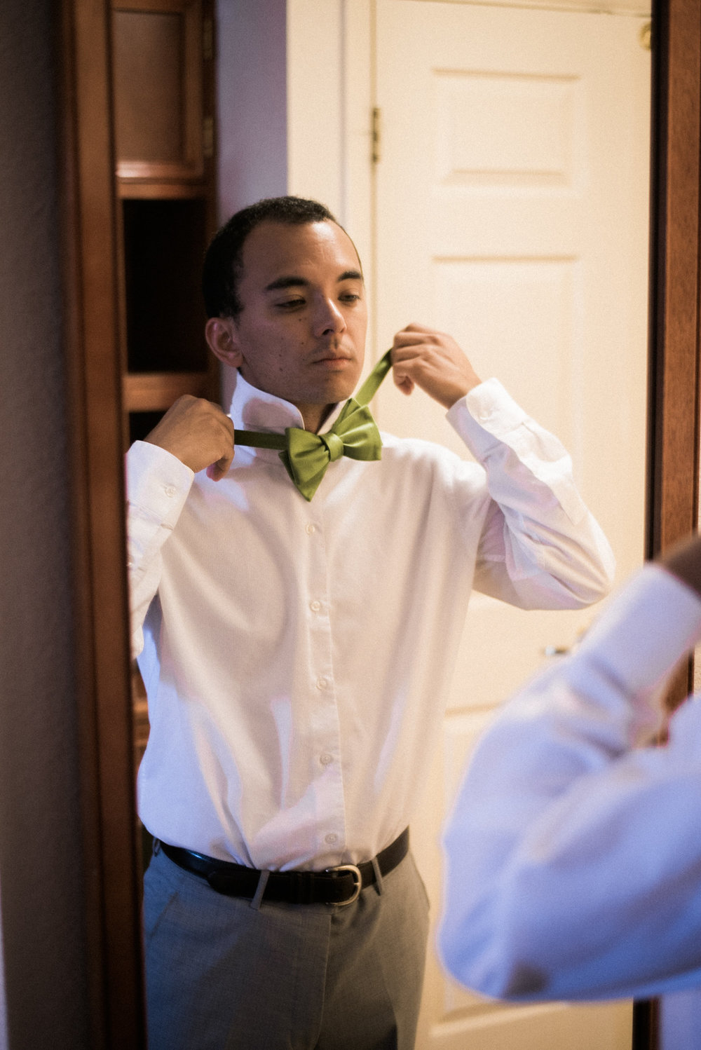 Groom tying bow tie