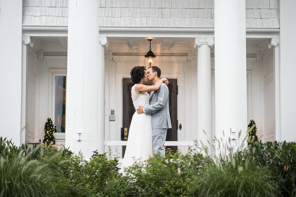 Bride and groom kissing on veranda