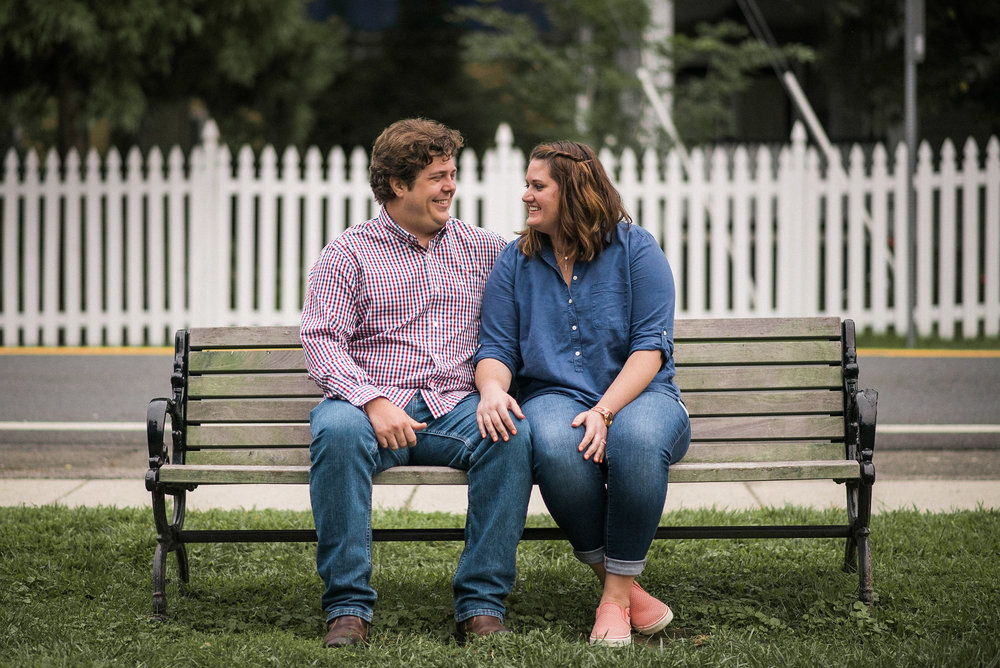 Couple sitting on bench in front of fence
