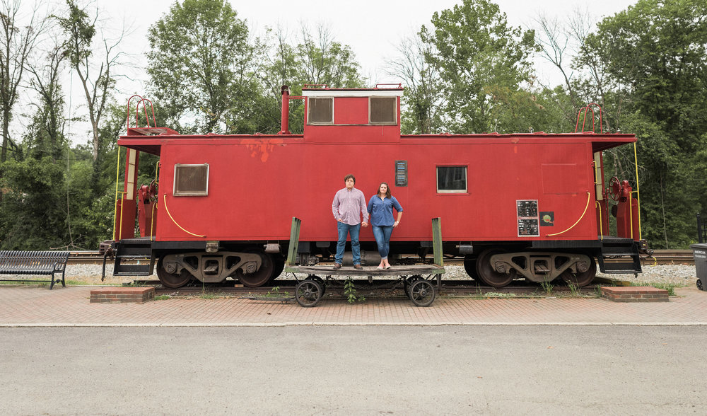 Couple standing on platform next to caboose