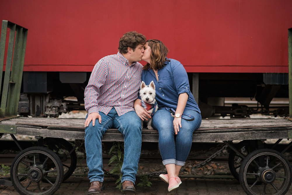 Couple kissing next to rail car