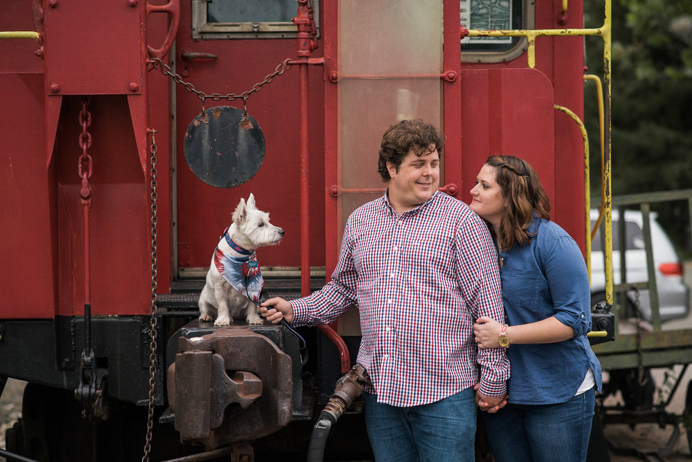 Dog looking at couple next to caboose