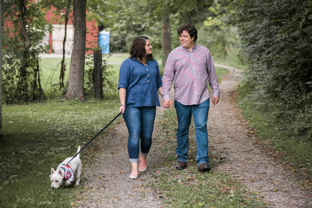 Couple walking on gravel path with dog