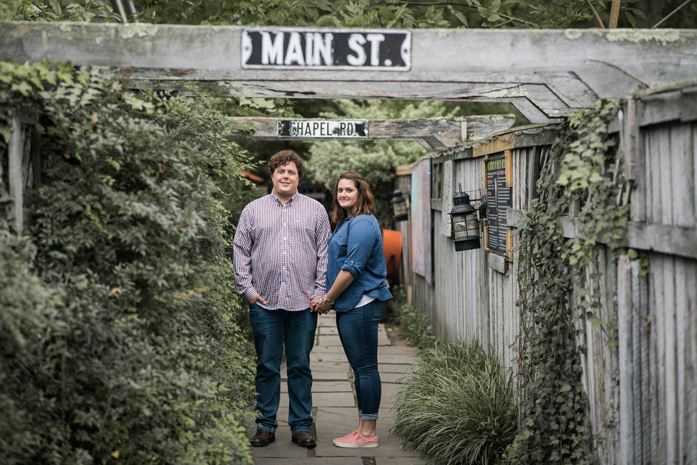 Man and woman standing under wooden pergola