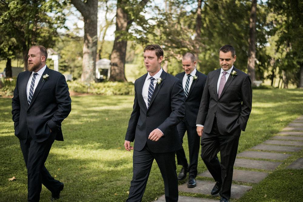 Groom and groomsmen walking across lawn