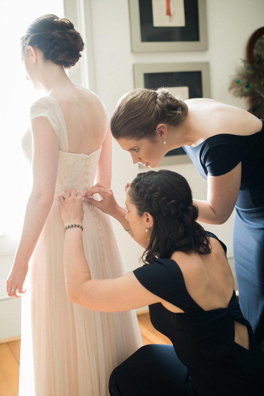 Bridesmaids zipping up bride