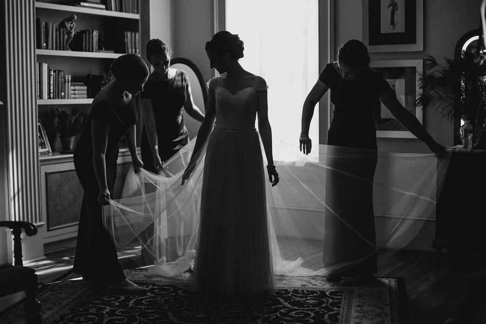 Bridesmaids holding bride's dress