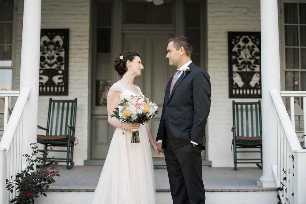 Bride and groom standing on porch