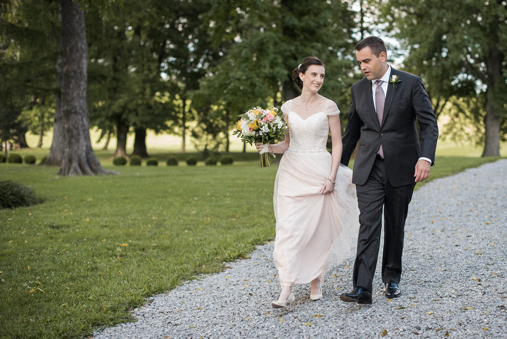 Bride and groom walking down gravel path
