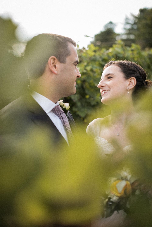 Bride and groom behind vines